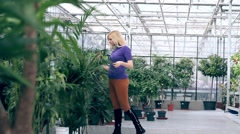 Girl choosing flowers to buy in greenhouse - stock footage
