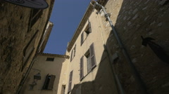 Low angle of the buildings on Rue Grande, near an arch in Saint-Paul-de-Vence Stock Footage