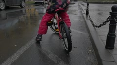 Child Sits on a Bicycle Legs in Pink Trousers Close up Wet Road Puddles Little Stock Footage