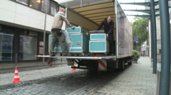 Workers transporting case boxes out of a truck - stock footage