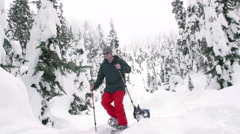 Man Snowshoeing in Mountain Backcountry with Dog Wearing Jacket - stock footage