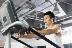 Young man working out in modern gym Stock Photos