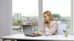 Smiling businesswoman with laptop and papers Stock Footage