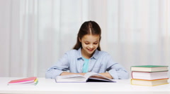 Happy school girl reading book or textbook at home Arkistovideo