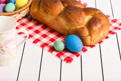Painted Easter eggs, delicious cake and cup for milk on a wooden background. Eco - stock photo