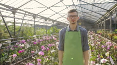 Confident man gardener in glasses standing in greenhouse with arms crossed. Slow Stock Footage