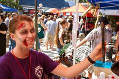 Woman Uses Mirror To Check Out Zombie Makeup At Event - stock photo