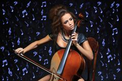 Pretty young female musician playing the cello - stock photo