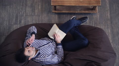 Attractive man talking on the phone while lying in a chair Stock Footage