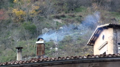 Smoke comes from the chimneys of old village house. - stock footage