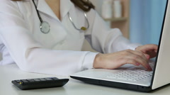 Woman doctor filling in health insurance form on laptop, calculating expenses - stock footage