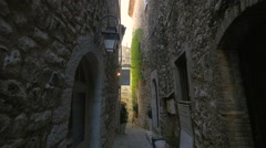 Tourists walking on a narrow street with stone buildings in Saint-Paul-de-Vence - stock footage