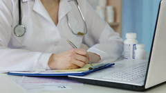 Doctor writing medical prescription, checking clinical records, signing papers - stock footage