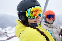Couple sitting on chairlift in mountain resorts - stock photo