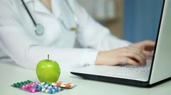 Physician using laptop in office, eating apple. Healthy diet, proper nutrition - stock footage