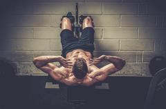 Muscular man doing exercises for abdominal in The Gym's Studio Stock Photos