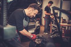Professional car  mechanic balancing car wheel on balancer in auto repair ser Stock Photos