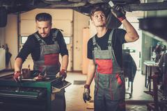 Profecional car  mechanics  working under lifted car in auto repair service. Stock Photos