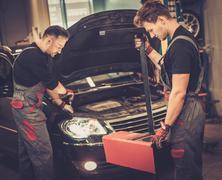 Professional car mechanics inspecting headlight lamp of automobile in auto re Stock Photos