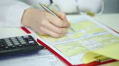 Stock Video Footage of Woman physician filling out papers, calculating patient's health insurance costs