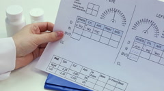 Ophthalmologist studying patient's eye test results, completing medical info Arkistovideo