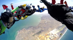 Group of skydivers are hovering in accelerated free fall above coastal city - stock footage