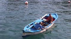 Men in a small boat fishing in Puerto harbor Stock Footage