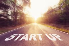 Asphalt blurred road and sunlight of Start Up for business concept. - stock photo