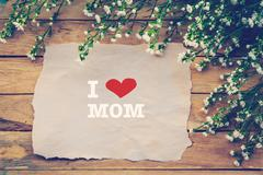 I love MOM and Happy Mothers day on brown paper with white flower on wooden b - stock photo