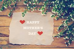 Happy Mothers day on brown paper with white flower on wooden board - stock photo