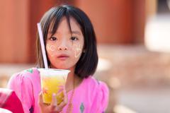 Thai little girl holding soda - stock photo