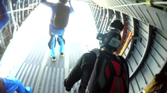 Group of skydivers is jumping out of airplane and hovering in free fall - stock footage