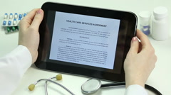 Doctor reading agreement, studying documents on tablet. Electronic documentation Stock Footage
