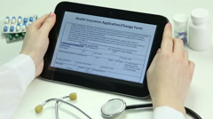 Doctor reading health insurance agreement on tablet. Electronic medical records - stock footage