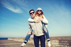 happy teenage couple in shades having fun outdoors - stock photo