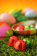 Chocolates and estar eggs on the grass Stock Photos