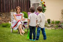 Beautiful mom, having coffee in a backyard, young cute child giving her prese Stock Photos