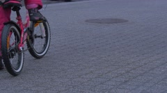 Kid's Legs Close up Child Sits on a Bicycle Pink Trousers Starts to Wheel Stock Footage