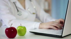 Woman doctor typing on laptop keyboard, eating an apple. Healthy way of living - stock footage