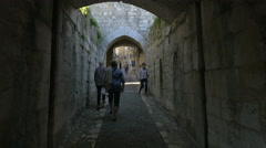Walking on a cobblestone arched street at Saint-Paul-de-Vence - stock footage