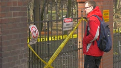 Backpacker Comes and is Standing at Fence Looking Behind the Fence at Park Bare - stock footage