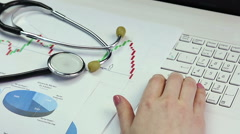 Medical scientist conducting research, comparing diagrams, working on laptop Stock Footage