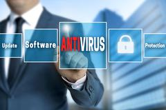 Antivirus touchscreen is operated by businessman Stock Photos