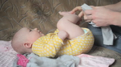 Young happy father dress his little daughter on sofa in bedroom - stock footage