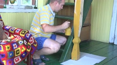 Male villager man painting pole in rural garden room with brush. 4K Stock Footage