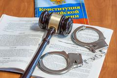 Judicial hammer, codes of laws  and handcuffs - stock photo