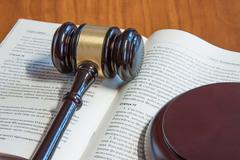 The judicial hammer lays on the  book - stock photo