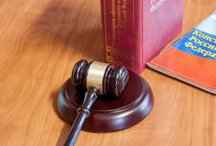 The judicial hammer and codes of laws lay on a table - stock photo