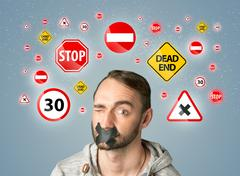 Stock Photo of Young man with glued mouth and traffic signals