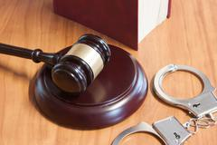 Judicial hammer, handcuffs and codes of laws - stock photo